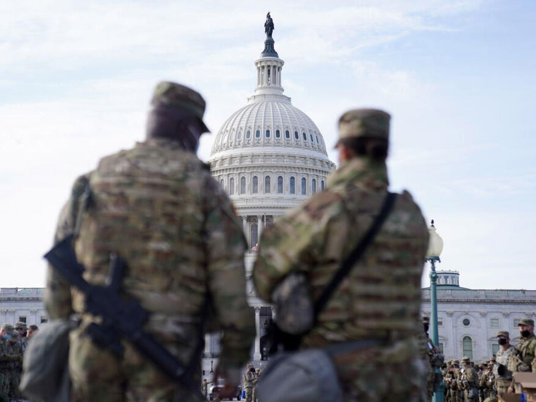 Two National Guard troops in the foreground frame a view of the Capitol dome in the distance.