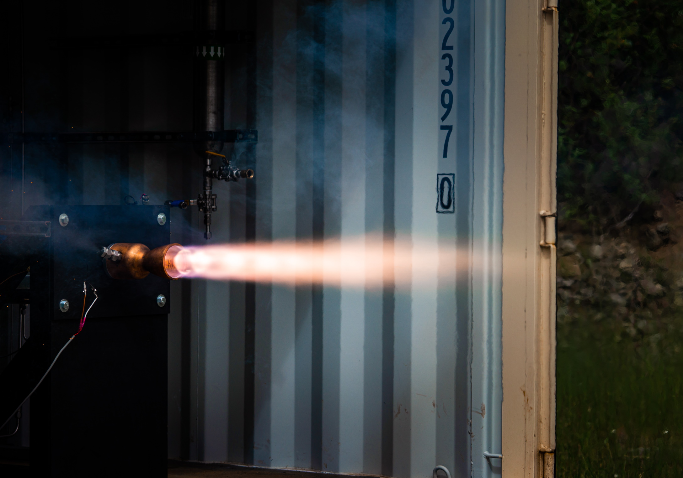 A missile makes a test fire in an industrial setting.