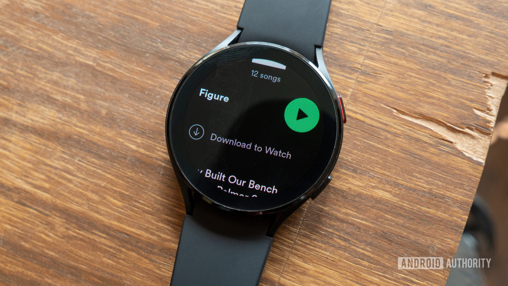 The Samsung Galaxy Watch 4 on a desk showing how to download Spotify music to Wear OS.
