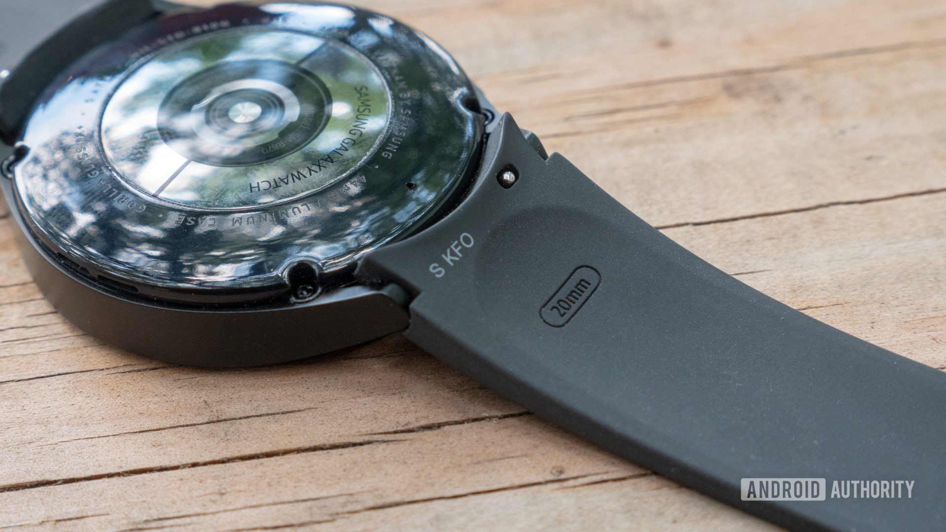 The Samsung Galaxy Watch 4 face-down on a table showing the silicone strap lug.